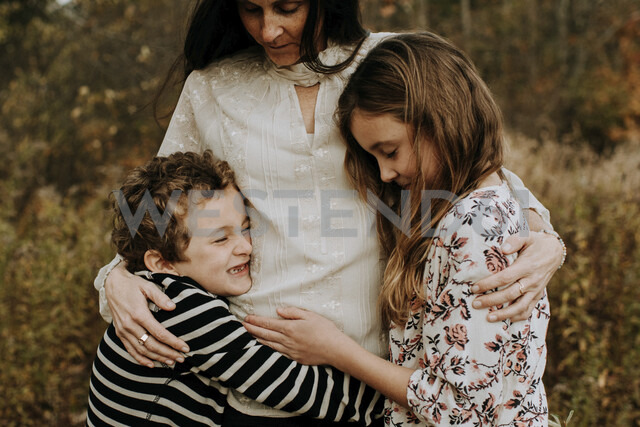 Side view of happy siblings with mother at park - CAVF54805