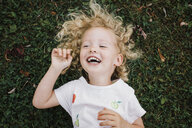 Close-up of cheerful girl lying on grassy field at park - CAVF54820