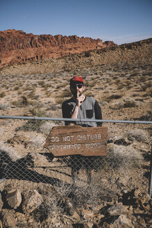 Man gesturing silence while standing by information sign on fence at Valley of Fire State Park during sunny day - CAVF54841