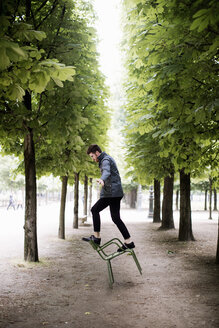 Side view of playful man balancing on tipping chair amidst trees at park - CAVF54868