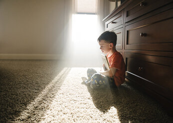 Side view of thoughtful boy with book sitting on rug at home - CAVF54886