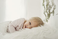 Portrait of cheerful girl lying on fur blanket at home - CAVF54946