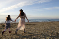 Rear view of mother and daughter holding hands while running at beach against sky during sunset - CAVF54952