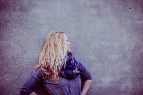 Portrait of a young woman with blonde hair standing against a wall - INGF07610