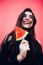 Fashion portrait of a pretty cool girl holding a slice of watermelon - INGF07616