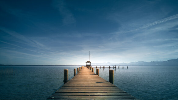 Tranquil scene of a wooden pier over a blue lake under blue skies in Bavaria - INGF07682
