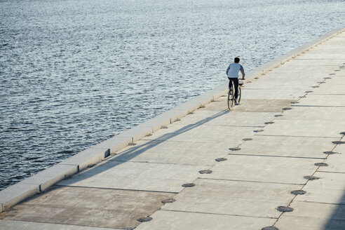 Young man riding bike on waterfront promenade at the riverside - VPIF01035