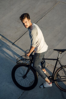 Young man with commuter fixie bike on concrete slabs - VPIF01041