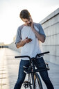Young man with commuter fixie bike looking at cell phone - VPIF01044