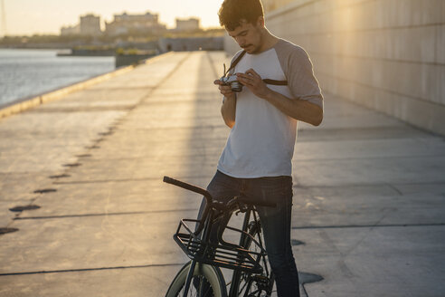 Young man with commuter fixie bike and camera on waterfront promenade at the riverside - VPIF01050