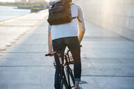 Rear view of young man with backpack riding bike on waterfront promenade at the riverside at sunset - VPIF01056