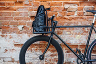 Backpack in cargo cage of acustomised commuter fixie bike at brick wall - VPIF01086