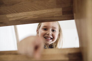 Portrait of happy little girl on stairs  at home - KMKF00640