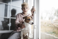 Portrait Jack Russel Terrier looking out of window while boy in the background watching - KMKF00643