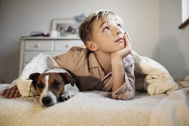 Portrait of blond boy and his Jack Russel Terrier lying together on bed - KMKF00649