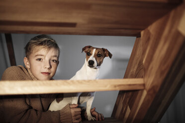 Portrait of boy with Jack Russel Terrier on stairs at home - KMKF00652