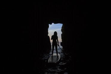 Woman paddle boardingin caves at sunset, La Jolla, San Diego, California, USA - AURF07710