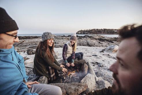 Friends relaxing around campfire, Portland, Maine, USA - AURF07803