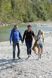 Family hiking with backpacks and a dog at the river Isar, Upper Bavaria, Germany - LBF02217