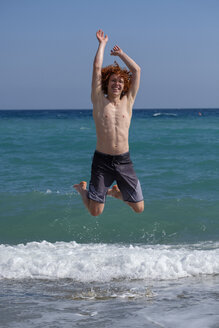 Portrait of redheaded young man jumping in the air at seashore - LBF02232
