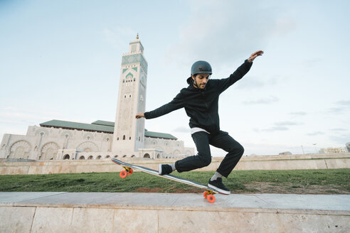 Full length of man performing stunt on skateboard against Mosque Hassan II - CAVF54974