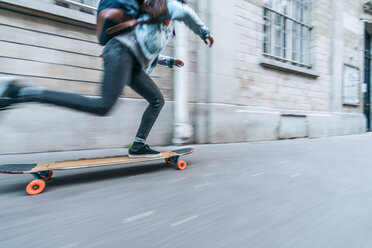 Blurred motion of woman skateboarding on footpath by building in city - CAVF54977