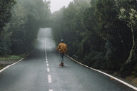 Rear view of man skateboarding on road amidst forest at Garajonay National Park - CAVF54986