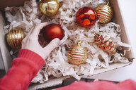 Cropped hand of woman taking bauble from box - CAVF55004