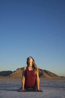 Woman practicing upward facing dog position against clear blue sky during sunset - CAVF55040