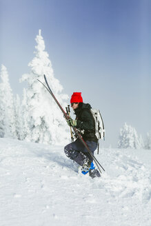 Side view of hiker with backpack and ski walking on snowy hill during winter - CAVF55046