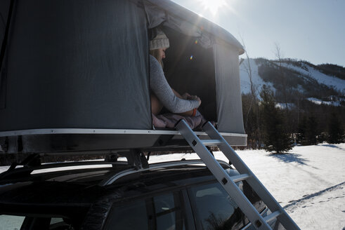 Woman sitting in roof tent on car during winter - CAVF55058