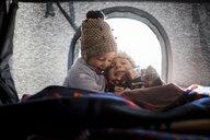 Smiling siblings sitting in roof tent - CAVF55061