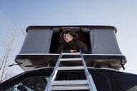Low angle view of man sitting in roof tent on car - CAVF55064