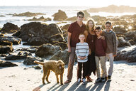 Portrait of happy family with dog standing at beach - CAVF55076