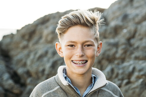 Portrait of smiling boy with braces at beach - CAVF55079