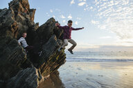 Playful boy jumping at beach while brother sitting on rocks - CAVF55082