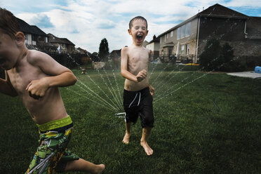 Shirtless brothers running by sprinkler at park - CAVF55139