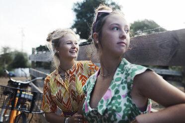 Female friends looking away by wooden fence - CAVF55151