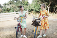 Female friends talking while standing with bicycles on field - CAVF55154