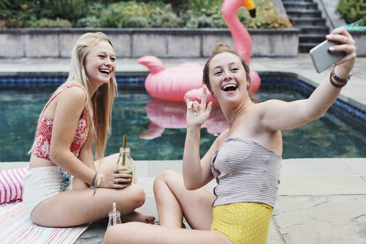 Happy friends taking selfie while sitting at poolside - CAVF55157 - Cavan Images/Westend61