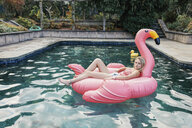 Portrait of teenage girl resting on inflatable swan at swimming pool - CAVF55160