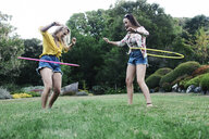 Low angle view of female friends spinning plastic hoops at park - CAVF55166
