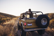 Rear view of female friends in off-road vehicle on field against clear sky - CAVF55211