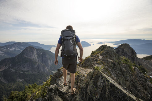 Rear view of hiker with backpack walking on mountain against sky - CAVF55253