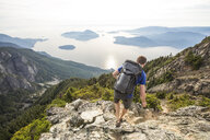 High angle view of hiker with backpack on mountain against sky - CAVF55256