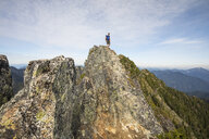 Low angle view of hiker standing on cliff against sky - CAVF55262