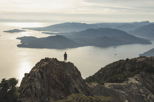 High angle view of carefree hiker standing on mountain against sky during sunset - CAVF55265