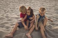 Siblings sitting on sand at beach - CAVF55271