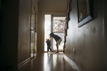 Siblings playing by door at home - CAVF55274