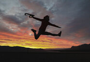 Excited hiker holding camera while jumping against dramatic sky - CAVF55310